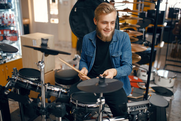 Young musician plays on drum set in music store