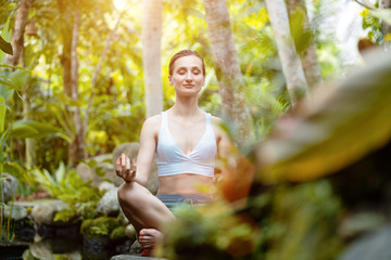 Woman doing yoga in the tropical jungle