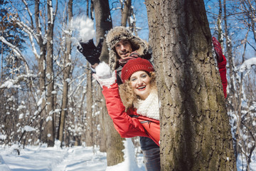 Woman and man in winter throwing snowball hiding behind a tree