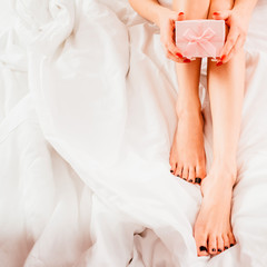 Woman special day. Female with bare legs sitting on bed with pink gift box.