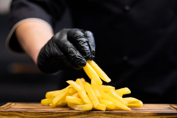 Traditional American fast food restaurant snacks. Cropped shot of chef in cooking gloves serving french fries on wooden board.