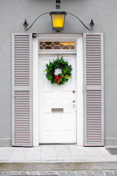 Clean white front door with Christmas wreath during Christmas holiday season