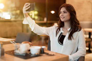 young beautiful woman in white stylish blouse looks shoots selfie while having meat burger with fries for lunch in trendy cafe eating outside
