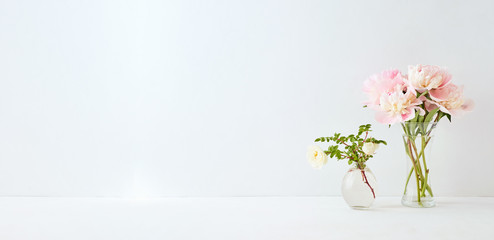 Home interior with decor elements. Pink peonies in a vase and white flowers on a white background