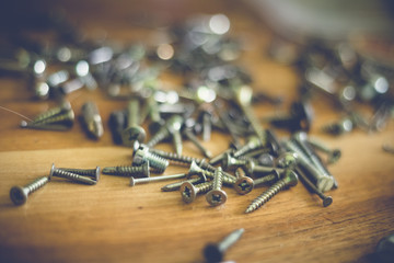 different types and sizes of nails and screws on a wooden table