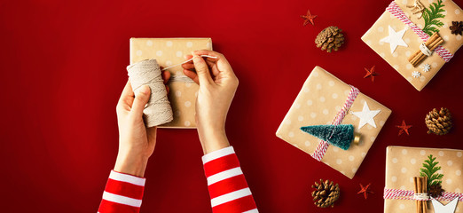 Wall Mural - Person making Christmas gift boxes - overhead view