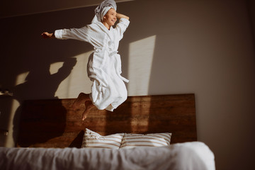 Beautiful joyful woman jumping happily on bed, looking away with cheerful expression, smiling brightly, raising leg high, having fun in bedroom, happiness lightness concept Wall mural