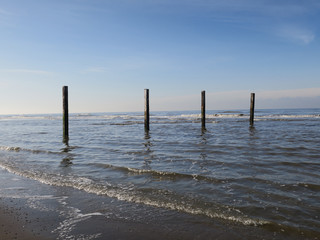 four wooden poles at the beach in the Northsea Zandvoort, The Netherlands