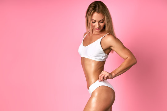 Attractive fitness woamn having good shaped body with tanned soft depilated skin, fising white penties, looking back, isolated on bink background, diet, health care, nutrition concept