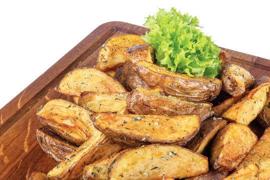 fried potato wedges or french fries. home made in rural style and served on on wooden board. healthy organic vegetarian food or beer snack. close up view