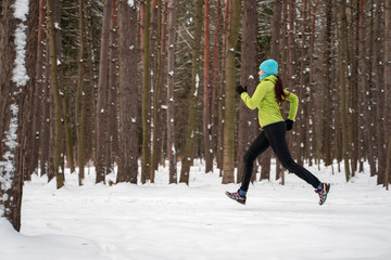 Image of young sportswoman running in winter forest