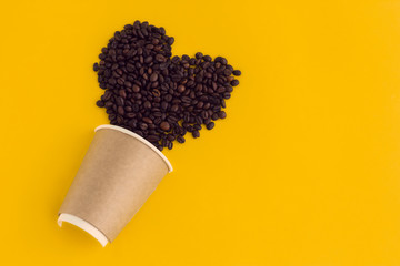 top view flat lay paper cup coffee with heart made of coffee beans isolated on a yellow background, coffee love and coffee addiction concept