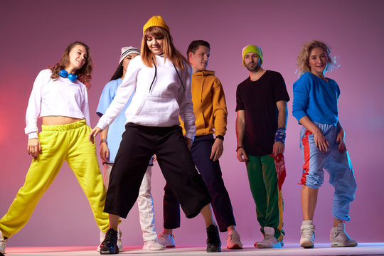 Young active people dressed in casual sport outfit, standing in full length on dance studio floor, expressing confidence over pink background, shot from below