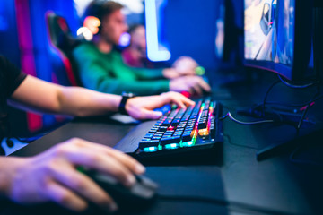 Obraz Professional cyber video gamer studio room with personal computer armchair, keyboard for stream in neon color blur background. Soft focus - fototapety do salonu