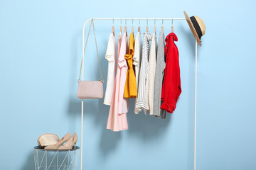 fashionable clothes on hangers on a wardrobe rack on a colored background. Wall mural