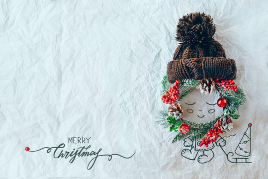 Christmas concept. Cute baby made of wreath of evergreen spruce, knitted hat and illustration on a white background. Minimal winter vacation idea. Flat lay top view composition.