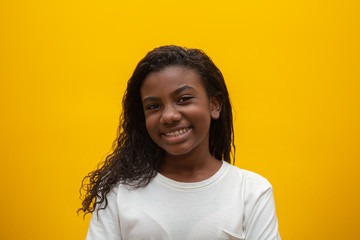 African American girl with curly hair on yellow background. Smiling black kid with a black power hair. Black girl with a black power hair. African descent.