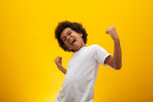 African American boy with black power hair on yellow background. Smiling black kid with a black power hair. Black boy with a black power hair. African descent.