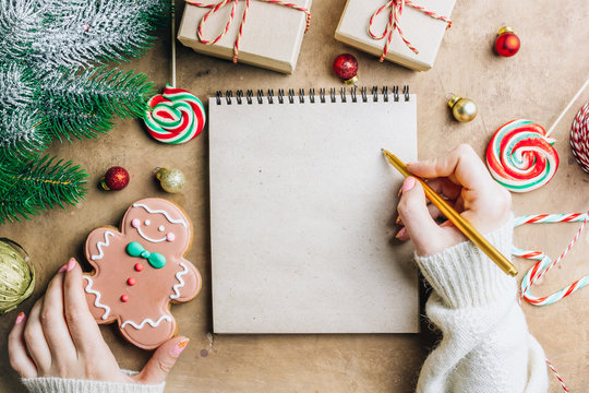 Notebook in the center of cute Christmas decoration: gift box, christmas balls, gingerbread man, fir tree branch, cande cane. Female hand writing in notebook. Flat lay. Top view