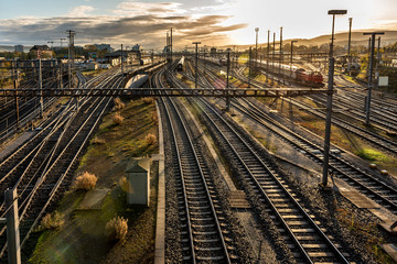 Foto auf Acrylglas Eisenbahnschienen Modern European railway station at sunrise with rail tracks and trains