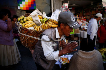 A man carries bananas at a street market in La Paz