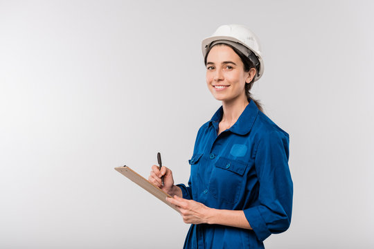 Happy young female builder in blue workwear and hardhat making notes in document