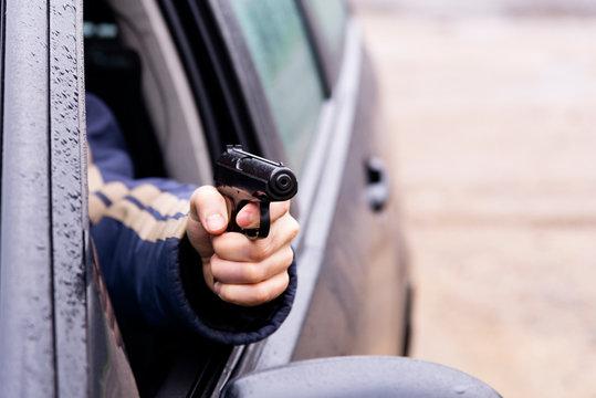 Man with a gun driving a car, male hand with a gun