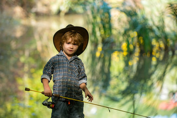 Little fisherman on a background of beautiful nature. A boy with a fishing rod and a cowboy hat. Happy fishing holidays with kids.