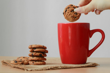 Female hand dipping cookies in red mug of milk.