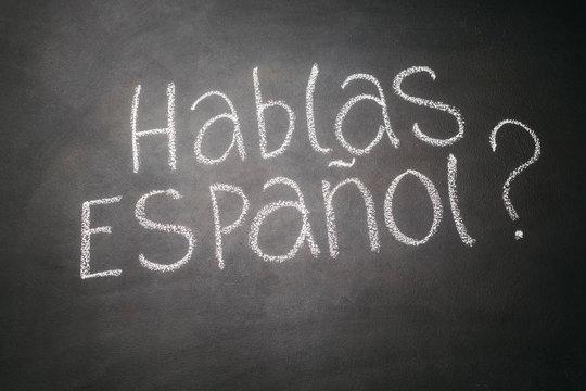 Spanish language learning concept. Inscription HABLA ESPANOL on blackboard.