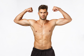 Sport, gym and strength concept. Sexy good-looking muscular young man in perfect shape, standing...