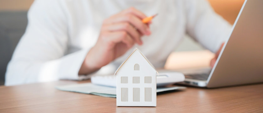 close up on house model with man working about  check and summary expense of home loan mortgage for refinance plan , people lifestyle concept