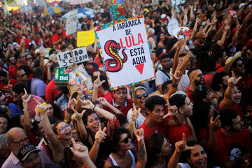 Brazil's former President Luiz Inacio Lula da Silva's supporters gesture and hold banners during a rally in Recife