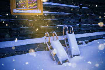 Merry christmas greetingcard with snow and sledges and a christmas tree behind a wooden hut window