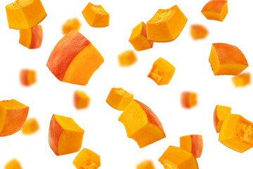 Falling piece of pumpkin, cubes, isolated on white background, selective focus