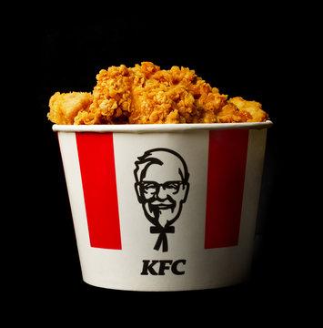 A lots of KFC chicken hot wings or strips in bucket of KFC (Kentucky Fried Chicken) fast food.