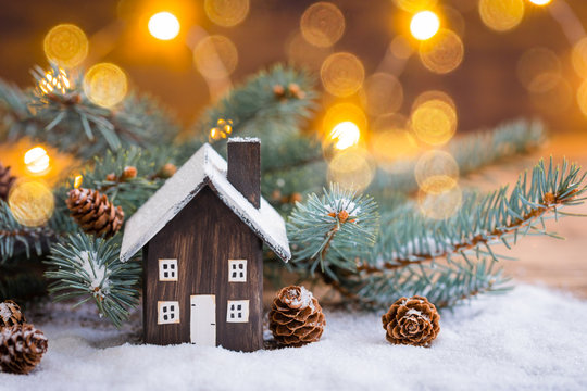 Miniature Christmas wooden house on the snow over blurred snowflakes background, toned
