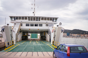 Ferryboat loading or unloading by a port pier. Concept of transportation and traveling.