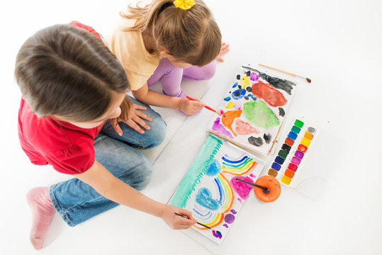 Children enthusiastically paint with watercolors