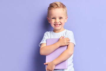 Portrait of blond kid boy holding book happily looking at camera , purple background. Kid involved in education Wall mural