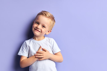 Portrait of little boy with blue eyes posing, smiling, look at camera. Children concept