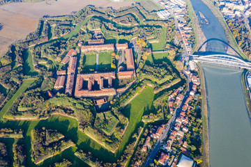 Aerial view of walls and bastions of modern six-star hexagon shaped fort Cittadella of Alessandria on winding river Tanaro. Piedmont, Italy. Bridge Ponte Meier connects fortress to town centre