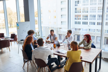 Young colleagues, caucasian business partners working as designers sit together at table in modern office with panoramic window. Papers, colorful pencils on table, active discussion