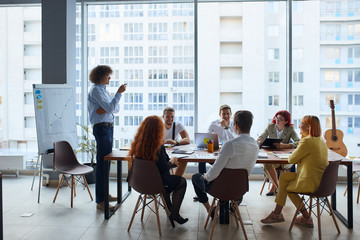 Young leader with curly hair wearing formal shirt giving instructions to colleagues sitting on table together and attentively listen to him, office background