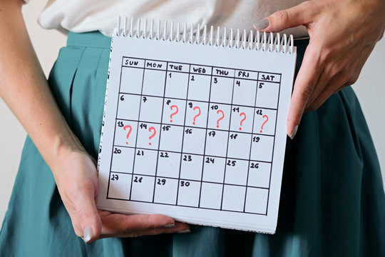 Woman holding calender with marked missed period. Unwanted pregnancy, woman's health and delay in menstruation.