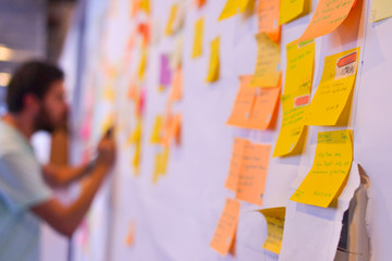 An agile software developer is updating Kanban board