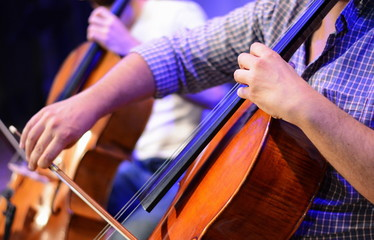 Professional cello player's hands close up, he is performing with string section of the symphony...