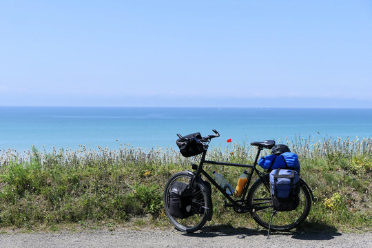 A moment to dream and a good mood. A lonely trekking bike is standing in front of wildflowers on a hill. In the background the blue sea rushes in the most beautiful sunshine.