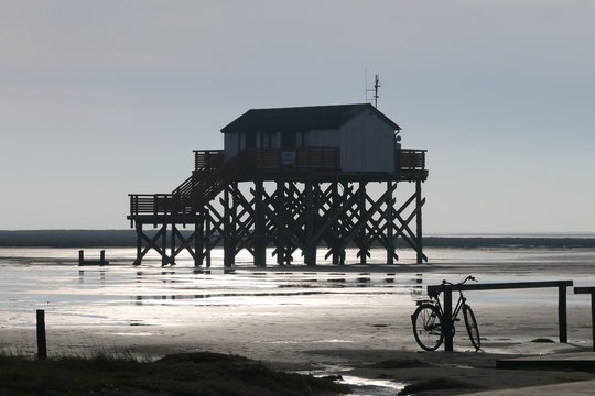 Fly at higher game. A stilt house with a staircase in cloudless sky and sunshine on the sea. At the pier is a lonely bike waiting for its owner. It's just low tide and absolute silence.