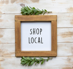 """The words """"Shop Local"""" in black text on a framed white board with white washed wood background and green leaves"""